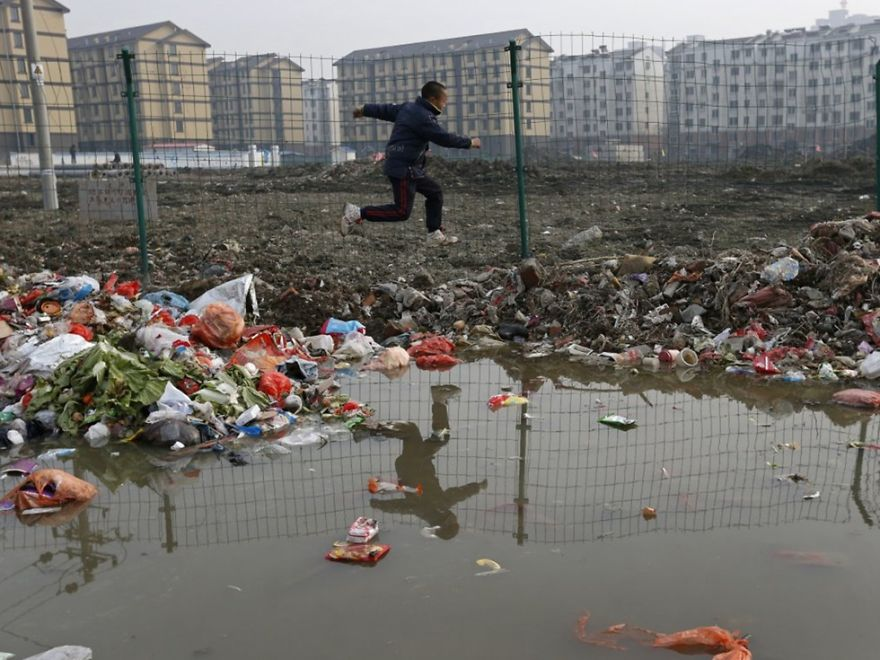 Child Jumps Over Trash At A Village, Jiaxing